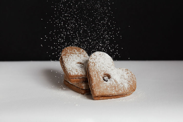 Sprinkling sugar on freshly baked homemade cookies Studio Shot Indoors  Food Still Life Food And Drink Close-up No People Black Background Brown Freshness Indulgence Sweet Food Baked Sugar Table Powdered Sugar Cookie Two Objects Ready-to-eat Cut Out Temptation Homemade Freshness Jam Freshly Baked Freshly Cookies