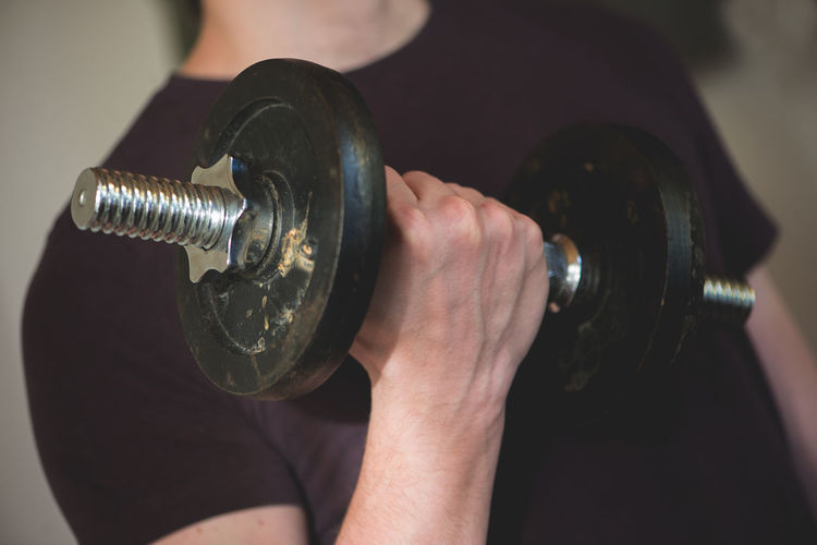 Midsection Of Man Exercising With Dumbbell