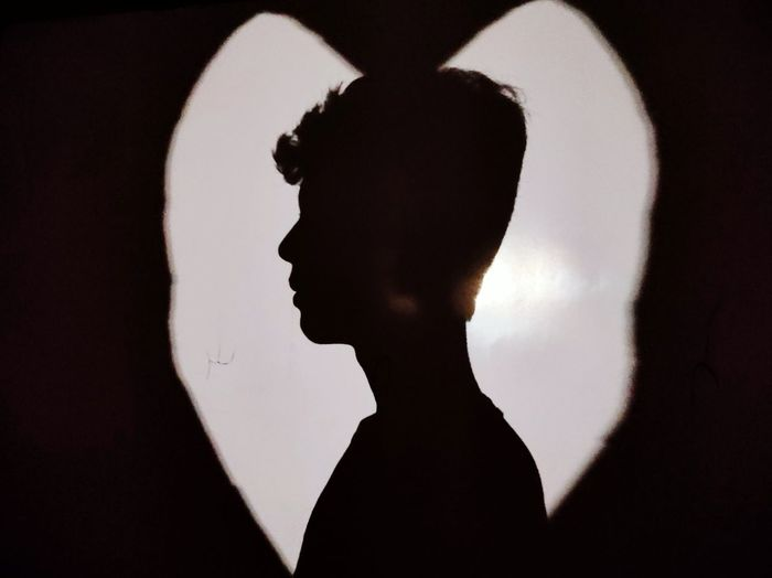 Close-up portrait of silhouette man standing against black background