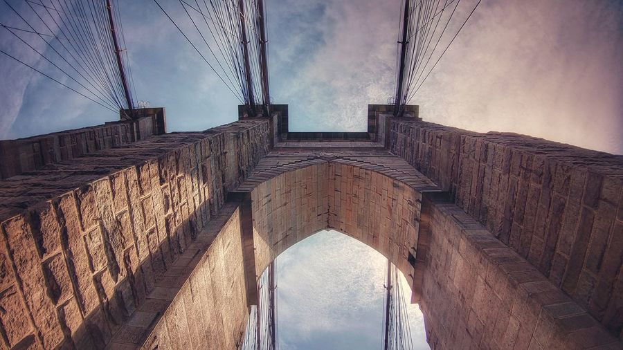 Low angle view of bridge and buildings against sky