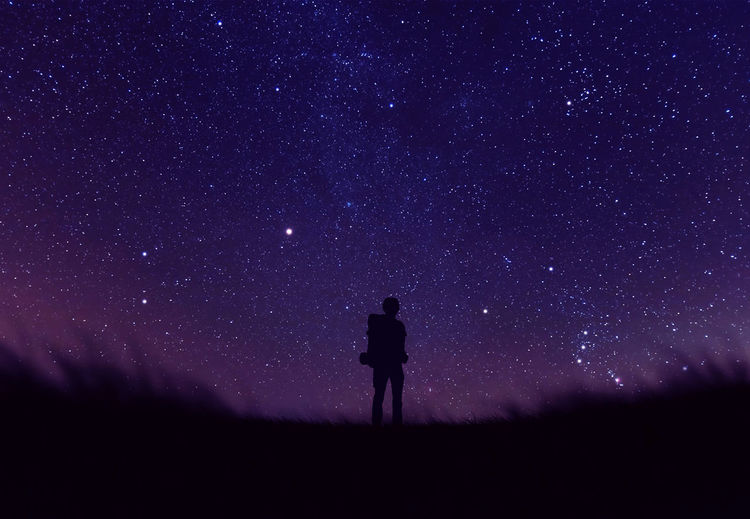 Low angle view of silhouette man standing against star field at night