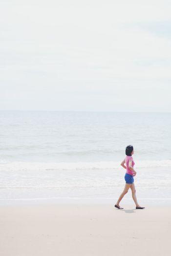 Side view of teenage girl walking at sea shore