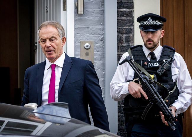 The day after the Chilcot Inquiry published its report on the Iraq War , Tony Blair under the watchful eye of an armed police officer, leaves his home in Central London Politics Westminster İnternational Relations Justice War