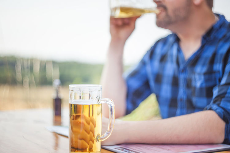 Midsection of woman drinking beer glass on table