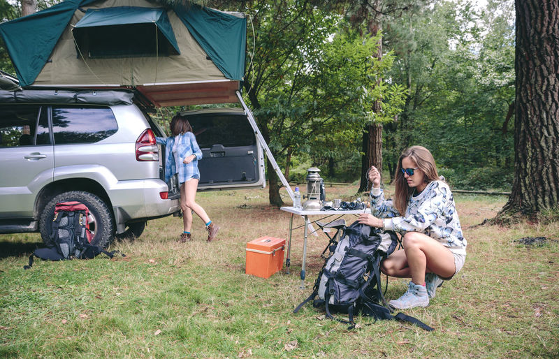Woman Packing Backpack While Friend Standing By Car In Forest
