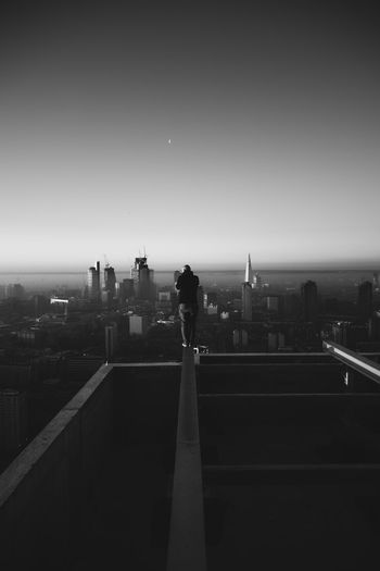 Silhouette of man standing on city buildings against clear sky