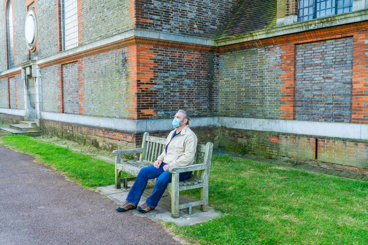 Man wearing mask sitting on bench against building