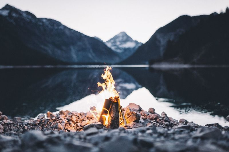 Campfire at the lake. Landscape Sunset Vscocam Flame Heat - Temperature Mountain Nature Bonfire Burning Camping Outdoors Sky No People Beauty In Nature Day Close-up Fire Pit Water