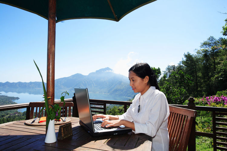 Woman using laptop while sitting against mountain and sky
