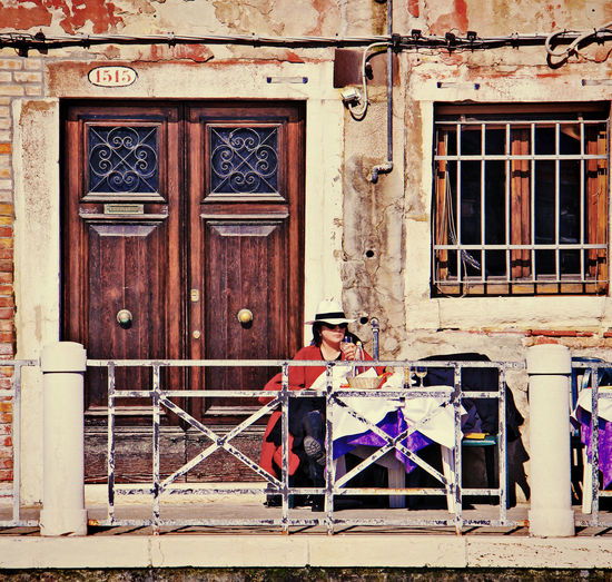 Every day life in Venice: a woman with a straw hat, sits alone enjoying herself in the sun outdoor sipping wine waiting for the meal. Adult Ancient Building Architecture Building Exterior Built Structure Day Door Doorway Enjoying Herself Lifestyles One Person Outdoors Passage Real People Restaurant Sipping Sitting Outside Straw Hat Table Terrasse The Street Photographer - 2017 EyeEm Awards Urban Venice, Italy White Wine In Wine Glass Young Woman