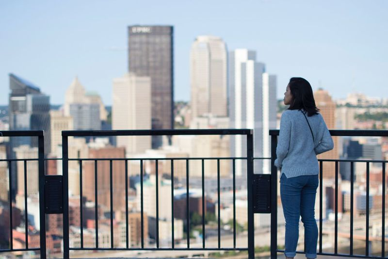 Rear view of woman standing against railing in city