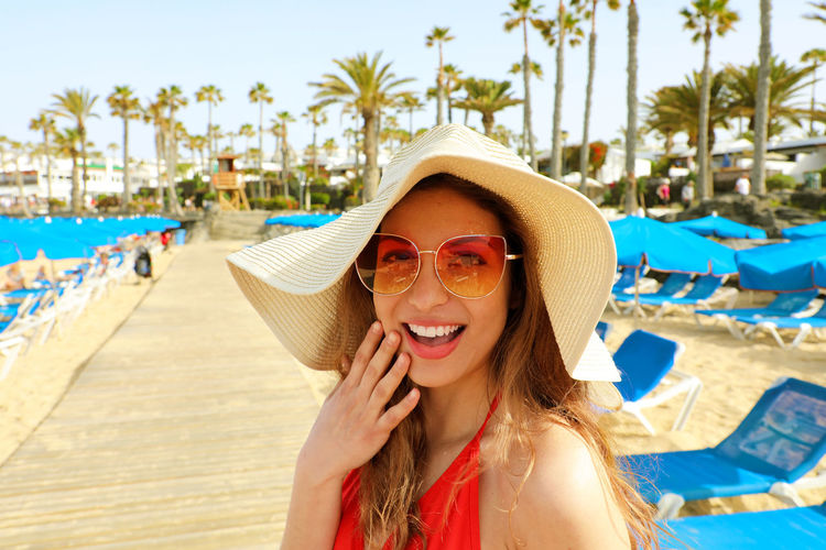 Beautiful woman excited in Lanzarote beach, Spain Excited For Summer Lanzarote Lanzarote Island Lanzarote-Canarias Beach Beautiful Woman Emotion Fashion Glasses Happiness Landscape Lanzarote Collection Leisure Activity Lifestyles One Person Palm Tree Portrait Smiling Sun Hat Sunglasses Young Adult Young Women