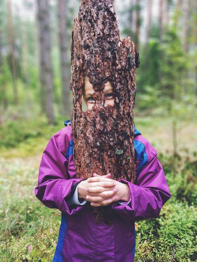 Portrait of girl holding tree bark