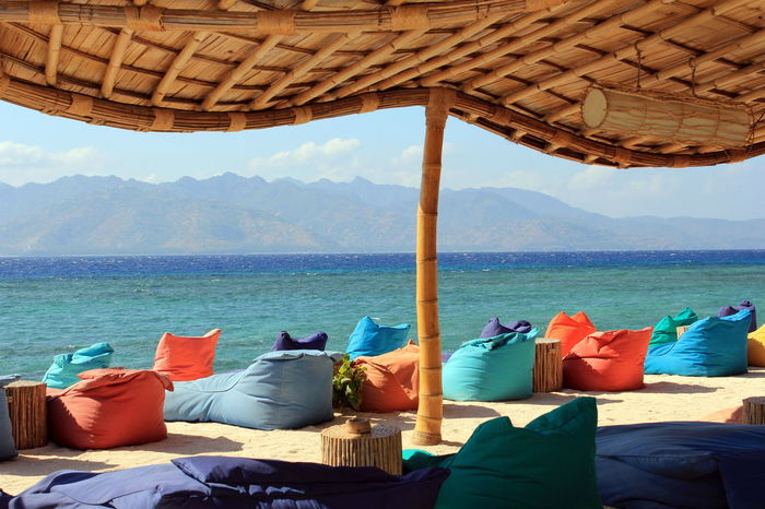 An area of relaxing bean bags in Gili Trawangan, Indonesia ASIA Beach View INDONESIA Quiet Beach Bean Bag Beauty In Nature Blue Chair Comfy  Day Gili Trawangan Hotel Beach Luxuirous Mountain Nature No People Ocean Outdoors Peacful Relaxation Scenics - Nature Sea Shade Tranquility