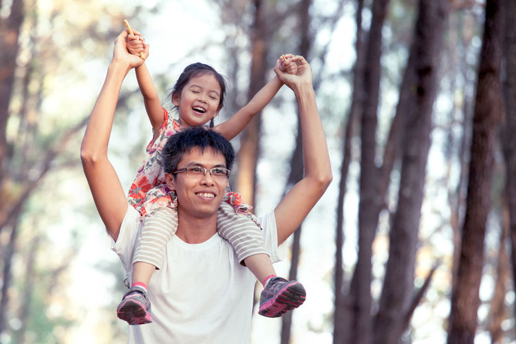 Father carrying daughter on shoulder against trees
