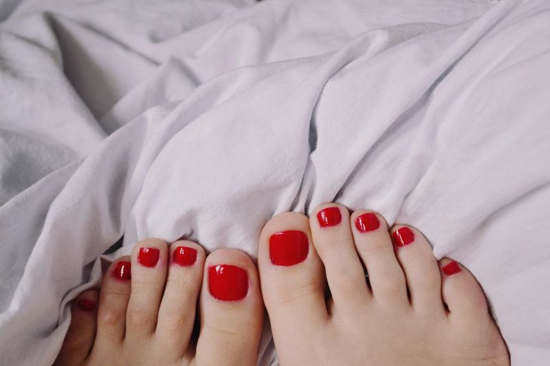 Low section of woman with red nail polish
