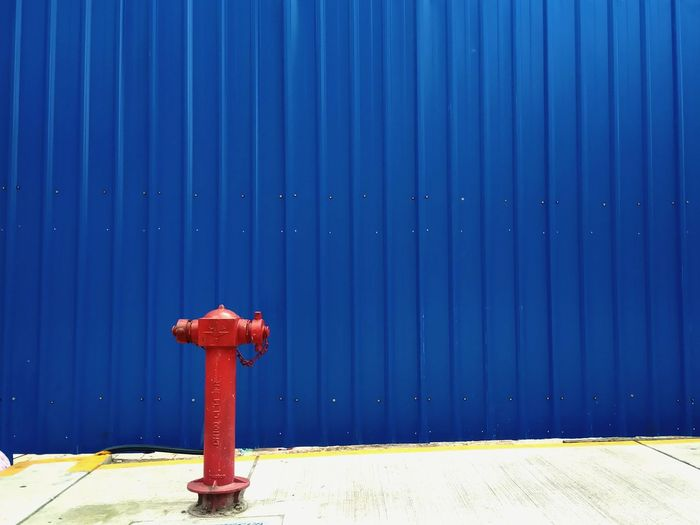 Close-Up Of Fire Hydrant On Footpath Against Blue Wall