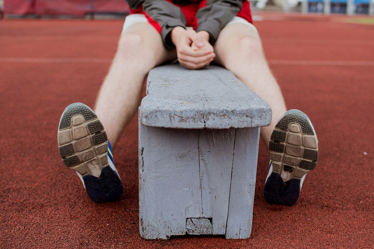 Low Section Of Boy Sitting On Bench At Stadium