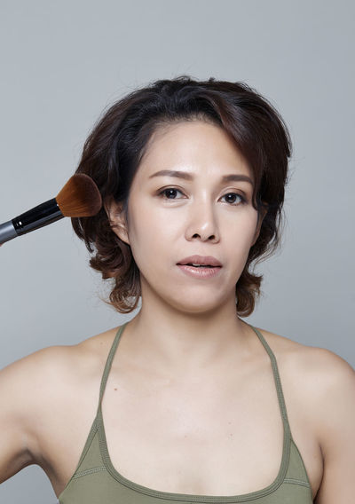 Portrait of beautiful woman applying make-up against gray background