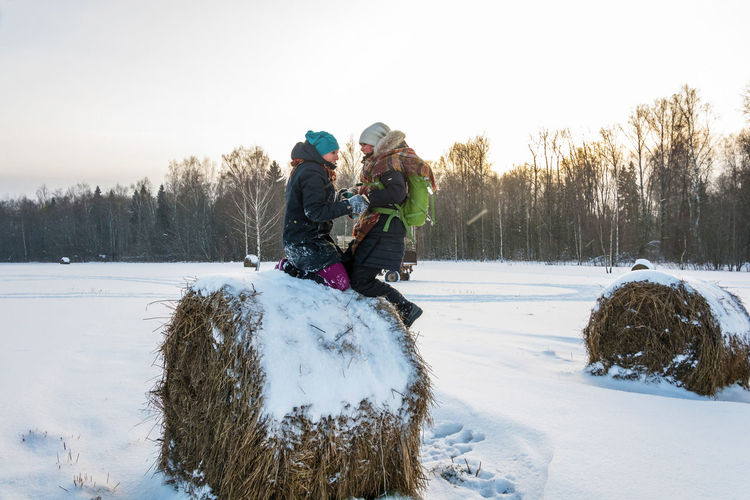 Side view of women kneeling on hay bale over snow covered land against trees during winter