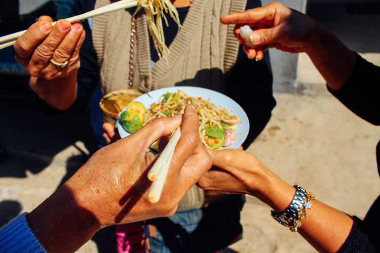 Cropped Hands Of People Eating Food