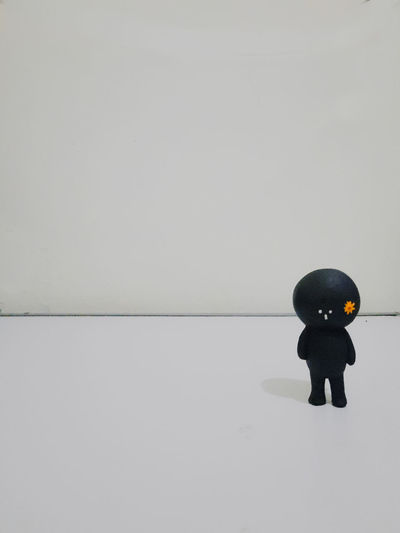 Boy standing by toy against white background