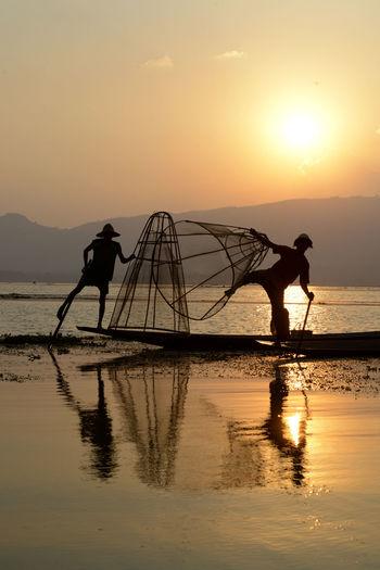 Silhouette men fishing in lake at sunset