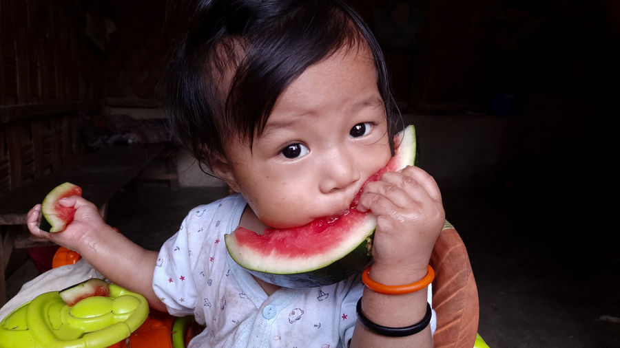Portrait of cute toddler eating fruit at home