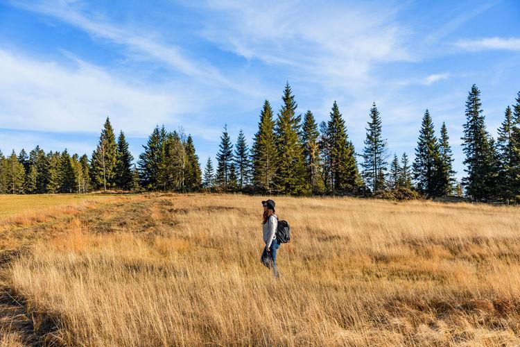 Young woman hiking through a field of golden tall grass.