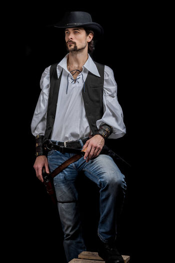 Handsome young man. This is an American cowboy. A vow to a white shirt, brown waistcoat and blue jeans. Black shoes on the feet. Carries a shtyapa, on a belt two pistols. The hair is of medium length; on the face is a beard and mustache. Authentic photo. Culture of America. Cowboy Wild West America American Gun National Authentic Moments Lifestyles Lifestyle One Person Candid Authentic Hat Black Background Three Quarter Length Front View Holding Clothing Young Men Young Adult Males  Men Weapon Handgun Jeans