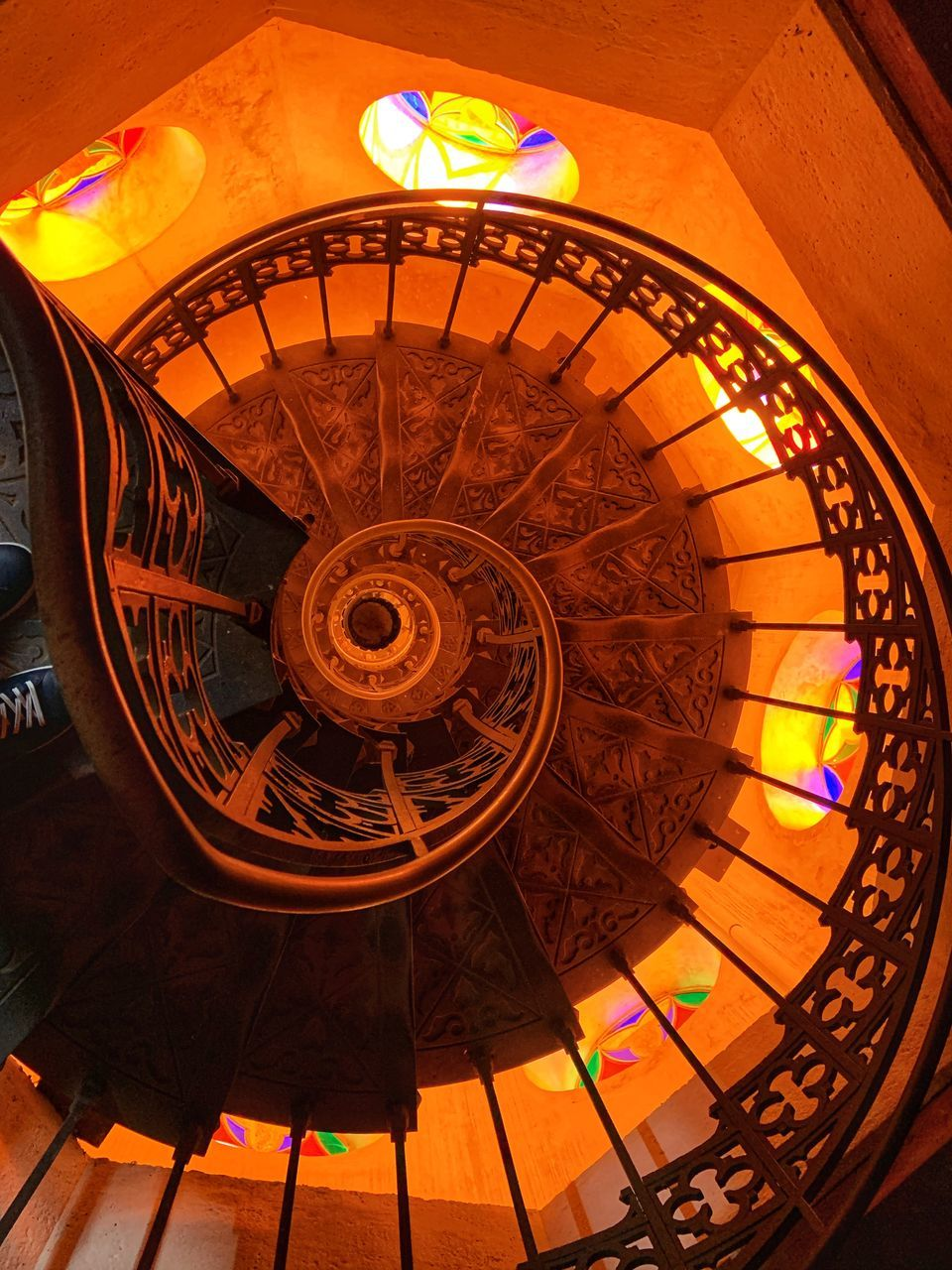 architecture, indoors, built structure, railing, steps and staircases, staircase, spiral, illuminated, no people, spiral staircase, pattern, low angle view, design, ceiling, arts culture and entertainment, lighting equipment, shape, directly below, day, ornate