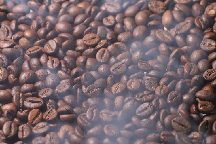 coffee beans texture with smoke of prepared hot coffee Coffee Beans Brown Bean Caffeine Drink Roasted Food Cafe Espresso Aroma Macro Seed Dark Beverage Morning Roast Closeup Breakfast Arabic Decaf Fresh Ingredient Many Natural Round Texture Harmony Roaster Flavor Freshness Grain Gourmet Stimulant Aromatic Quality Harvest Energy Background Full Cafeteria Group Pattern Crop  Abstract Handful Backdrop Smoke Prepared Hot