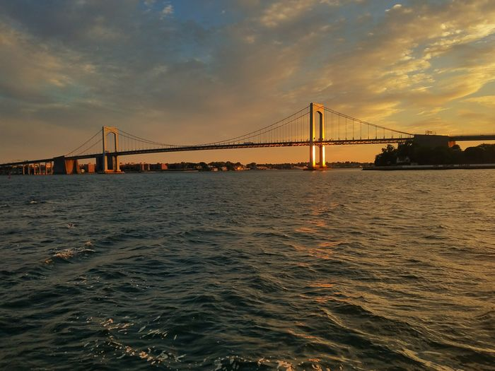 Throgs Neck Bridge glowing in the distance. Photo taken from a boat (7/6/2018) Urban Skyline Water Sea Sunset Horizon Illuminated Cable-stayed Bridge Calm