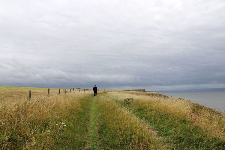 Man Walking On Field By Sea Against Sky