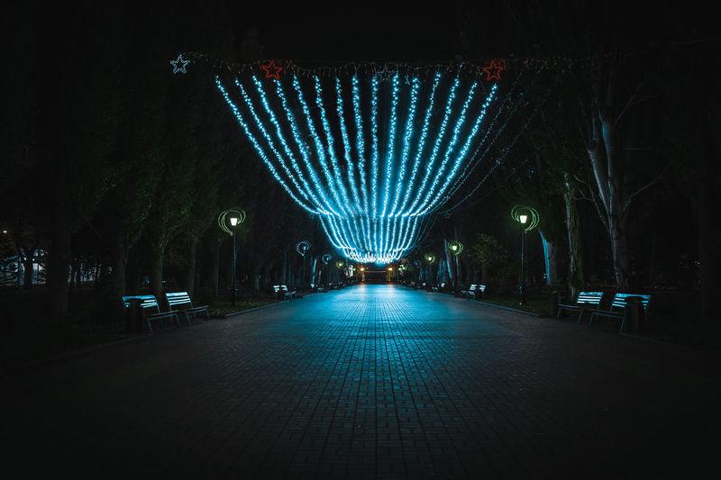 Illuminated footpath in city at night