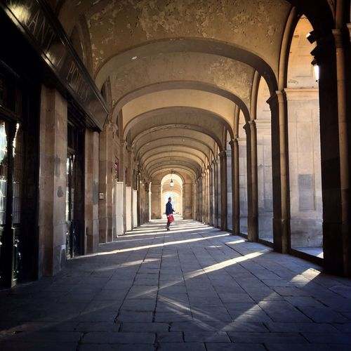 Side view of man walking in corridor at an arched structure