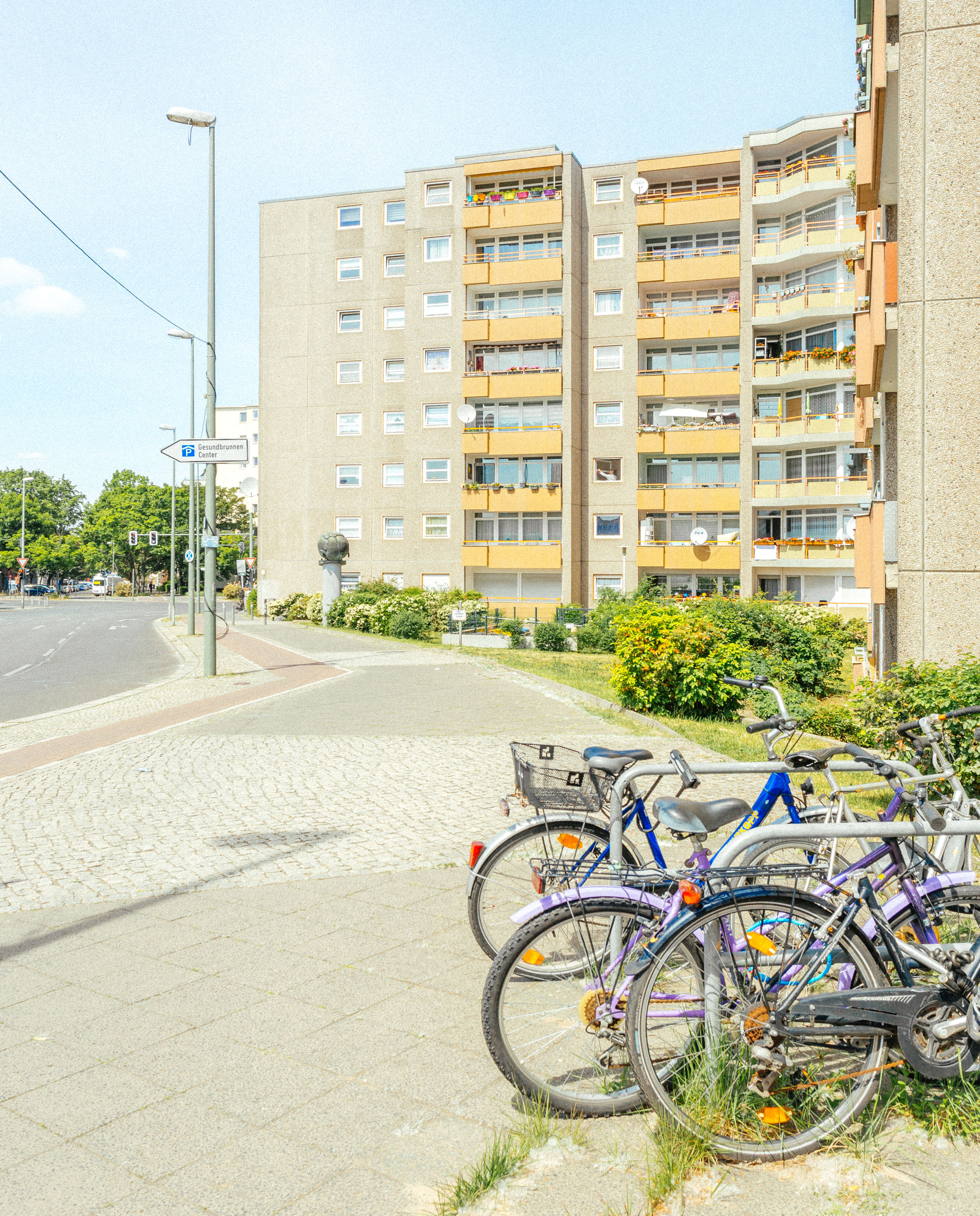 architecture, building exterior, city, bicycle, built structure, transportation, residential area, building, street, mode of transportation, vehicle, neighbourhood, land vehicle, nature, residential district, city life, day, no people, bicycle wheel, road, sky, city street, apartment, plant, outdoors, sports equipment, urban area, parking, sunlight, office building exterior, lane, travel, wheel, office, sunny, house, cityscape, tree, suburb, cycling