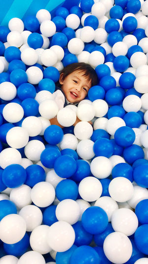 High angle view portrait of smiling boy in ball pool