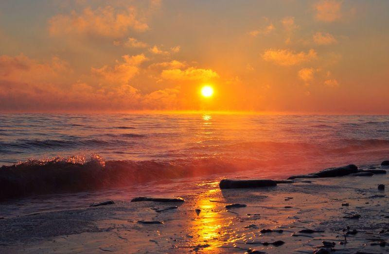 Waves breaking on beach against cloudy sky at dusk