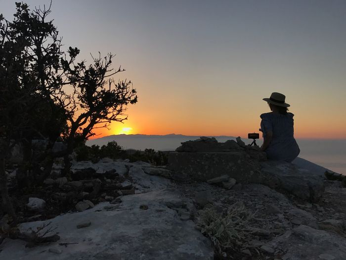 Rear view of woman sitting on rock against sky at sunset