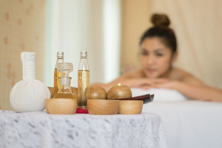 Massage oil in bottles by bowls on table in spa