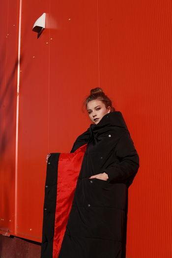 Fashionable Teenage Girl Wearing Black Warm Clothing Standing Against Red Wall During Sunny Day