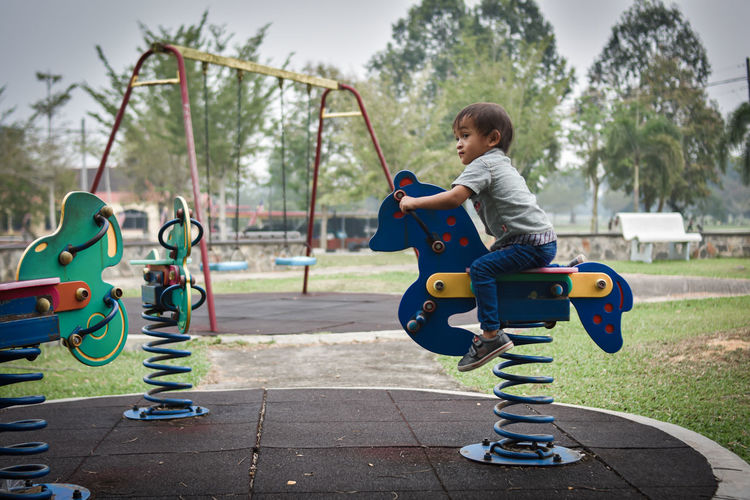 Boy looking away while sitting on rocking horse on playground