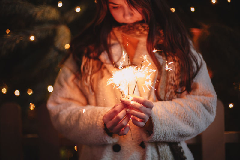 Midsection of woman holding sparkler at night