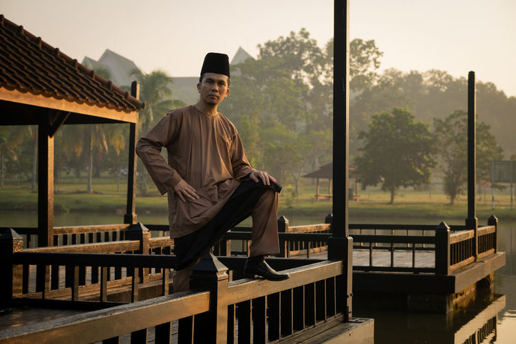 Portrait Of Man Wearing Traditional Clothing While Standing On Built Structure Against Lake During Sunset