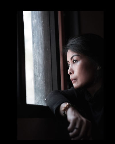 Thoughtful woman looking through window