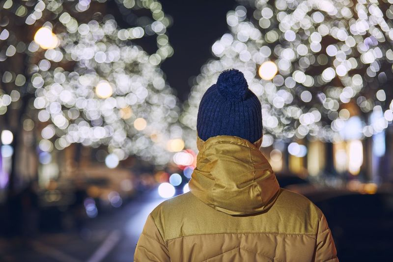 Rear view of person standing by illuminated tree at night