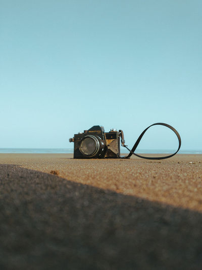 Close-up of camera on beach against clear sky