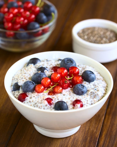 Chia ( hispanica) seed pudding with blueberries and redcurrants in bowl, photographed on dark wood with natural light (Selective Focus, Focus one third into the pudding) Chia Dessert Pudding Raw Redcurrant Salvia Hispanica Seed Snack Berry Berry Fruit Blueberry Breakfast Currant Food Food And Drink Fresh Fruit Healthy Healthy Eating Meal Milk Red Currant Sweet Sweet Food Uncooked