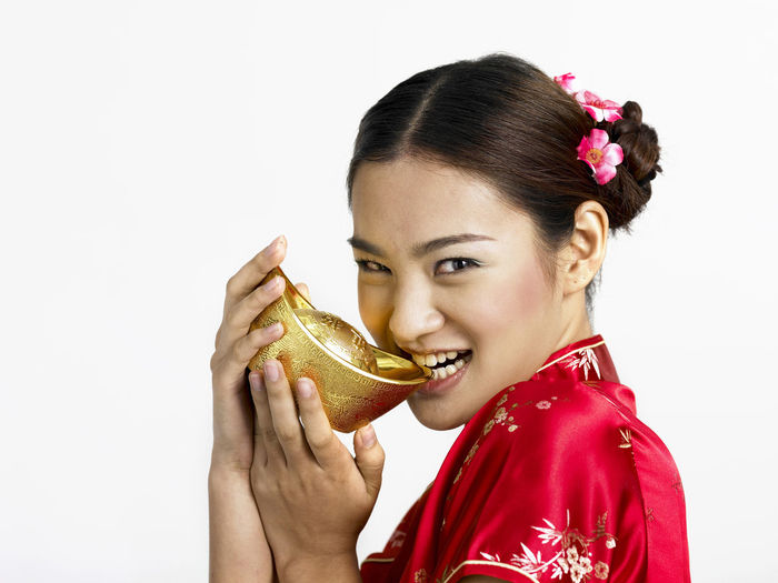 chinese woman holding gold ingot Gold Gong Xi Fa Cai New Year Prosperity Red Treasure Adult Cheongsam Chinese New Year Close-up Day Fortune Freshness Hair Bun Headshot Heritage Holding Looking At Camera One Person Portrait Qipao Studio Shot White Background Young Adult Young Women